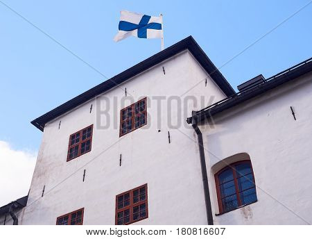 Finnish Flag On The Roof Of The Turku Castle In Finland In Bright Sunshine