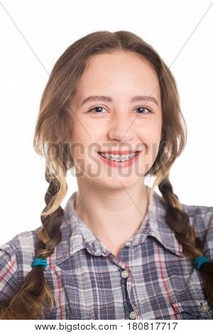 A cute piggy girl in a checkered shirt shows her braces. Isolated on white. Dental concept