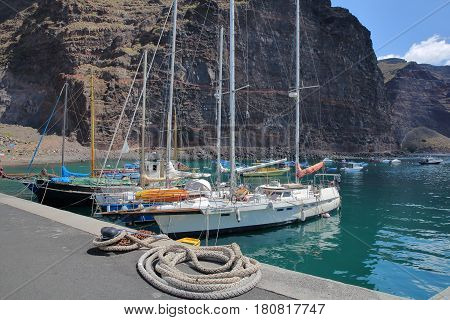 VALLE GRAN REY, LA GOMERA, SPAIN - MARCH 19, 2017: The village of Vueltas with sailing boats and cliffs in the background