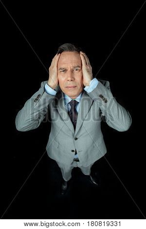 Overhead View Of Middle Aged Frightened Businessman In Suit On Black