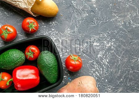 fresh vegetables in plastic tray from store on gray desk background top view mock-up