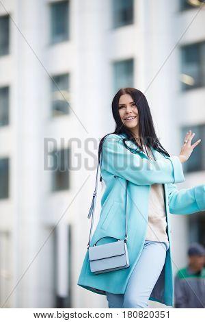 Spectacular brunette walking along street near building