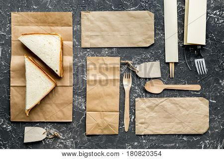 food delivery service workdesk with paper bags and sandwich on gray background top view