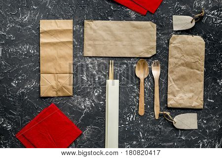 delivery service set with paper bags and flatware on gray desk background top view