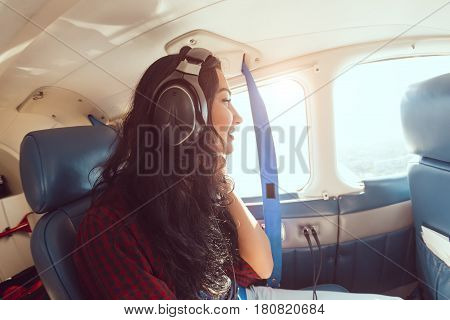 Female airplane passenger enjoying the view from the cabin window of small sport plane. Young brunette woman in headphones sitting in plane during flight