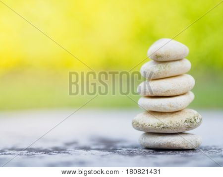 Balance Stones stacked to pyramid in the soft green background to Spa ideas design or freedom and stability concept on rocks.