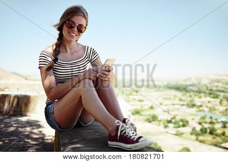 Young joyful female tourist using gps navigation on her smartphone having rest on hill's peak. Concept of holidays and technology.