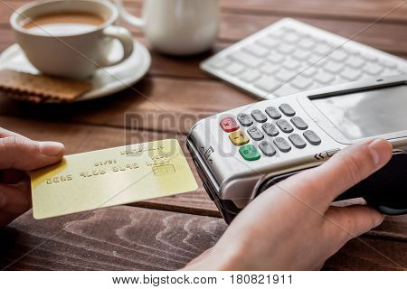 Buy coffee with credit card and payment terminal in cafe on wooden table background