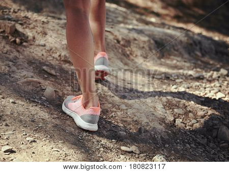 Hiker step on the ground. Young female backpacker traveling in mountain terrain, walking on rough trail.