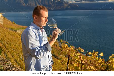 Man holding a glass of wine. Lavaux, Switzerland