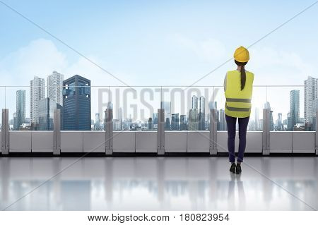 Portrait Of Asian Woman With Yellow Helmet Standing On Terrace