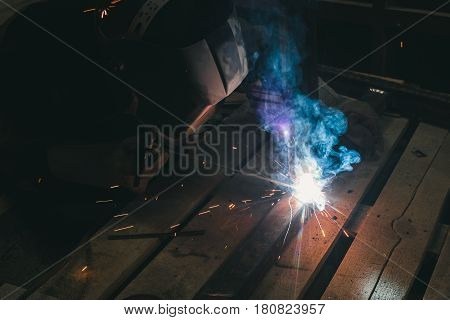 The electric welder does the work at the factory. Worker in special protective gear