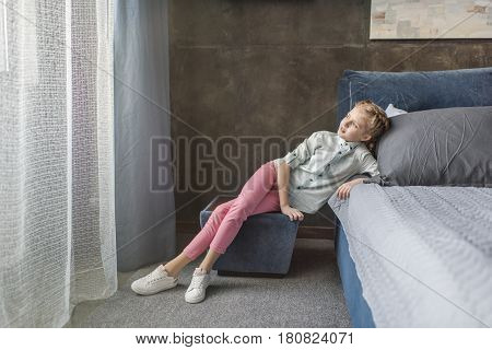 Pensive Adorable Girl Sitting On Pouffe Near The Bed At Home