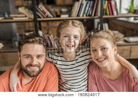 Happy Young Family With One Child Embracing And Smiling At Camera