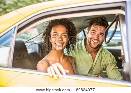 Interracial couple driving on a taxi in Manhattan - Tourists sightseeing New York on a yellow cab