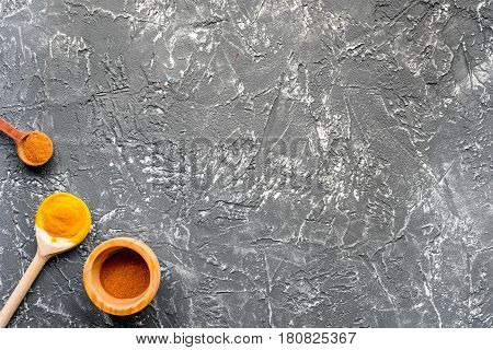 Professional kitchen with spices in spoons for cook concept on gray desk background top view mock-up