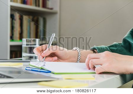 Taking notes in copybook at home working place. Female person hand writes in notebook sitting at the table indoors in front of laptop
