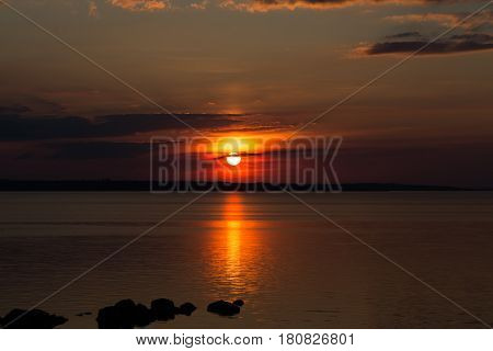 Fantastic red black sunset on the background of black clouds. Sunny path on the water surface. Big sun on the sky horizon. Dark stones in the water. Reservoir. Dnipro. Ukraine night