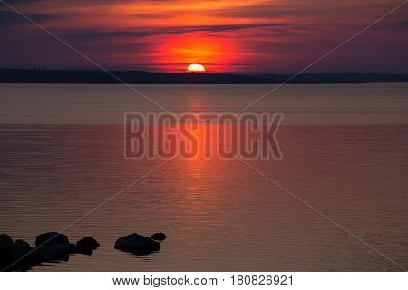 Dramatic red black sunset above the water surface. Big sun on the horizon. Dark stones in the water. Reservoir. Dnipro. Ukraine