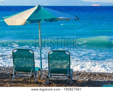 two beach chairs and umbrella on the shore of a pebbly beach Greece Rhodes