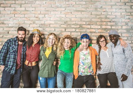 Group portrait of multi-ethnic boys and girls with colorful fashionable clothes holding friend in hands and posing on a brick wall - Urban style people having fun studio shot - Concepts about youth and togetherness