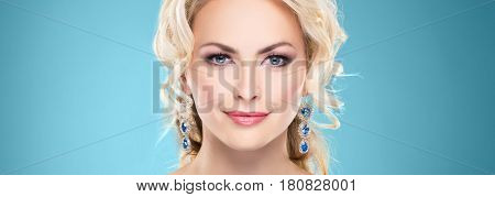 Beautiful blond girl with luxury golden necklace over cyan background.