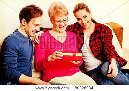 Happy family - couple with old woman who holding gift box
