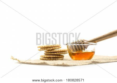 The Honey Dipper And Fragrant Honey Into A Transparent Bowl With Cracker Isolated White Background.