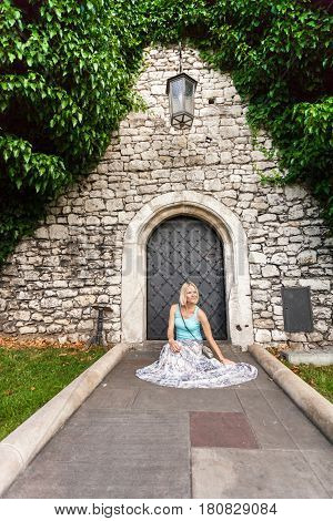Young beautiful blonde woman in blue t-shirt and long skirt against the background of a stone old wall with a small vintage door and with ivy. Woman sitting on the floor
