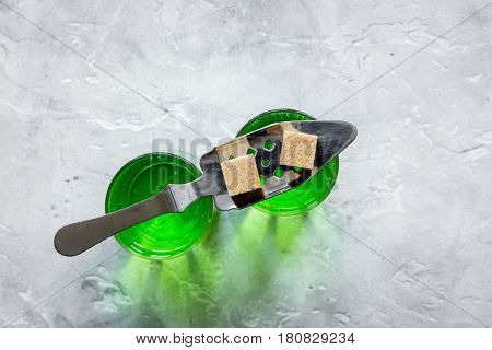 green absinthe shots with sugar cubes on stone bar table background top view mock up
