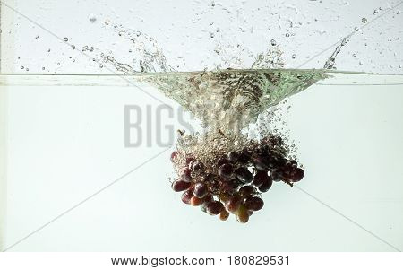 Bunch of grapes splashing into water on white background