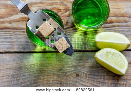 green absinthe with sugar cubes in spoon on wooden table background top view