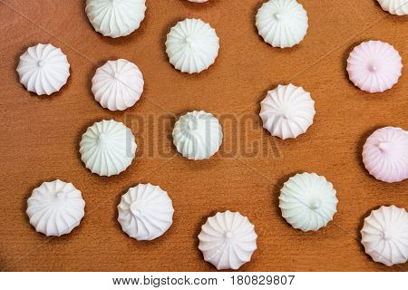 Meringue pattern on wooden background. Top view