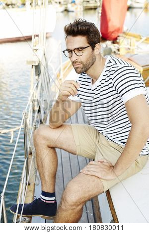 Dude on boat in harbor looking away
