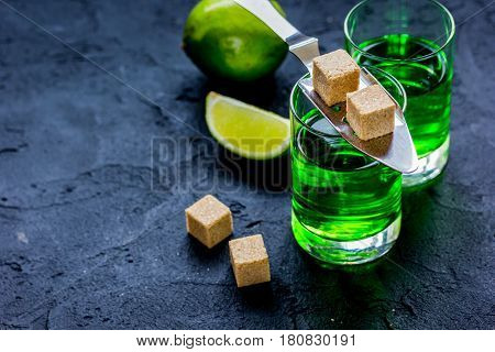 absinthe shots with fresh green lime slices and sugar cubes on dark bar table background mock-up