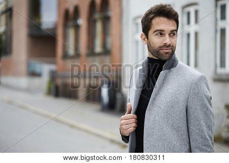 Smiling guy in grey overcoat looking away