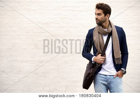 Handsome dude in scarf and jacket looking away