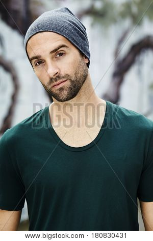 Handsome guy in hat and green tee portrait
