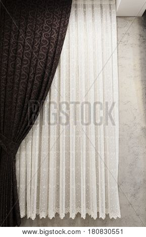 Beautifully draped long curtain on the window in the room. Close up of piled curtain. Luxury curtain home decor. Brown panels. White lace drapery