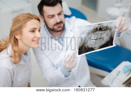 Do you spot this anomaly. Private capable competent dentist showing his future colleague scans of his patient explaining her some specifics and asking for her opinion
