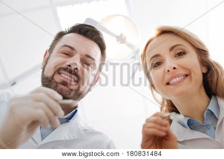 Twice as good. Two prominent neat dentists looking at their patient asking her opening her mouth while she lying on the dentists chair