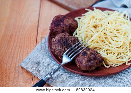 Beef cutlets with spaghetti in a rustic style. Mitbols with paste on a ceramic plate. Meat cutlets on a wooden background.