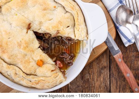 Homemade meat pie from puff pastry with beef and vegetables on wooden table Top view
