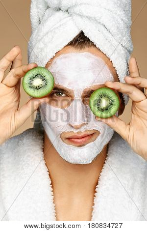 Man with facial mask and kiwi slices on his eyes. Photo of well groomed man receiving spa treatments. Beauty & Skin care concept