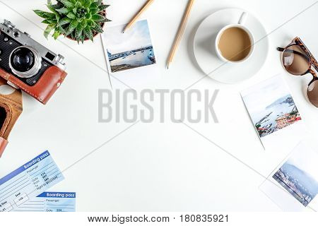 tourist stuff with cup of coffee, camera and photos on white table background top view mock-up
