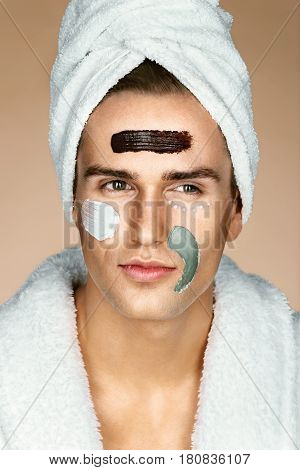 Fashionable man with three different face masks (chocolate cream and clay masks). Photo of man with perfect skin. Grooming himself
