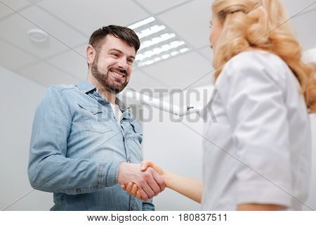 Was nice working with you. Delighted doctor and her happy patient shaking hands with a doctor and expressing his gratitude after undergoing some dental procedures