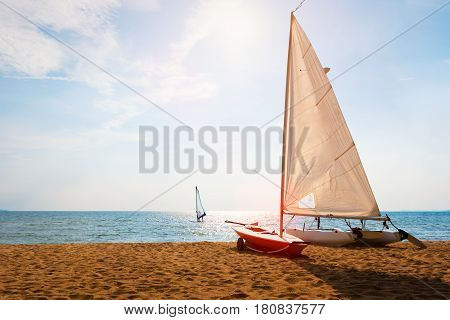 Sailboat on beach and sky background with windsurfing in the wind through the waves at the sea. International Laser Class sailboat also called Laser Standard and the Laser One on beach