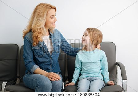 Behave like an adult. Supportive loving gentle mother talking to her child and fixing her hair while distracting her from nervous thoughts before meeting a doctor
