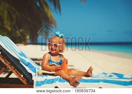 cute little girl with sunblock cream on tropical beach
